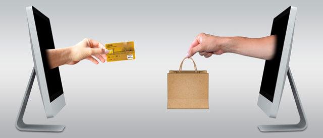 dos ordenadores, de los cuales salen dos manos reflejando la compra online